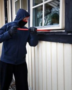 Burglar braking into a house